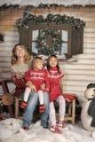 Mutter mit zwei Mädchen auf einer Bank nahe dem Haus Stockfotografie