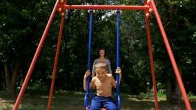 Mutter reiten ihren kleinen Sohn auf ein Straßen-Schwingen am Spielplatz in der Zeitlupe stock video footage