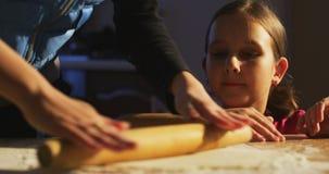 Mutter rollt den Teig und die unterrichtende Tochter, um zu kochen stock footage