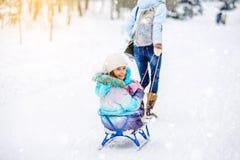 Mutter rollt ihre kleine Tochter auf dem Schlitten im Winter Stockfoto