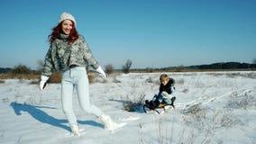 Mutter rollt ihren Sohn auf einem Schlitten, einer glücklichen Familie im Winter, einer Spaßunterhaltung für die Mutter und einem stock footage