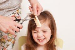 Mutter schneidet Tochter ` s Haar zu Hause Lizenzfreie Stockfotografie