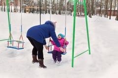 Mutter schwingt ihre Tochter auf einem Schwingen an einem Winternachmittag draußen im Park Lizenzfreie Stockfotografie