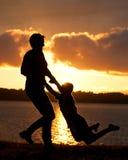 Mutter schwingt Sohn im Sonnenuntergang Stockbild