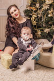 Mutter sitzt unter dem Baum mit einem kleinen Kind in einer Geschenkbox Lizenzfreie Stockbilder