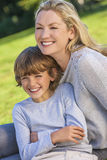 Mutter-Sohn-Frauen-Jungen-Kind, das draußen im Sonnenschein sitzt Lizenzfreie Stockfotos