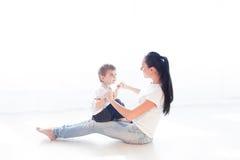 Mutter spielt mit ihrem Sohn auf dem Boden des Glückes stockfotografie