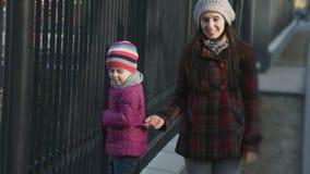 Mutter spielt mit ihrer Tochter, das Mädchen, das entlang den Zaun geht Aufbau mit Schrauben und Muttern stock footage