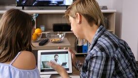 Mutter spricht mit ihrem Doktor über ihre Tochter ` s Gesundheit durch einen Videoanruf auf einer Tablette stock video