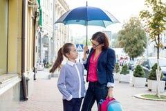 Mutter spricht mit ihrer Tochter für zehn Jahre auf ihrem Schulweg Vor dem hintergrund der Stadt unter einem Regenschirm Lizenzfreie Stockfotos