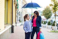 Mutter spricht mit ihrer Tochter Vor dem hintergrund der Stadt unter einem Regenschirm Lizenzfreies Stockfoto