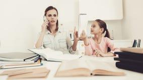 Mutter spricht am Telefon Tochter ` s Hausarbeit-Aufgabe lizenzfreie stockbilder
