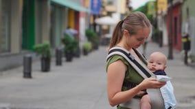 Mutter steht auf der Straße mit einem Baby in einem Riemen und den Blicken am Handyschirm und bedrängt den Schirm mit stock video footage