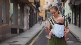 Mutter steht auf der Straße mit einem Baby in einem Riemen und den Blicken am Handyschirm und den Blicken durch die Fotos stock video