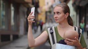 Mutter steht auf der Straße mit einem Baby in einem Riemen und schießt ein Video für soziale Netzwerke über seine Reise zu stock video