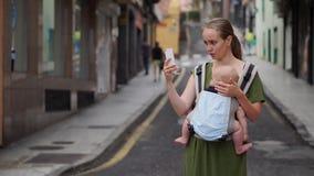 Mutter steht auf der Straße mit einem Baby in einem Riemen und schießt ein Video für soziale Netzwerke über seine Reise zu stock footage