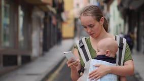Mutter steht auf der Straße mit einem Kind in einem Riemen und den Blicken am Handyschirm stock footage