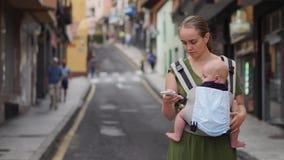 Mutter steht auf der Straße mit einem Kind in einem Riemen und den Blicken am Handyschirm und steht in Sozial in Verbindung stock video