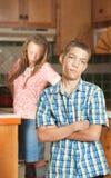 Mutter steht mit den Händen auf Hüften in der Küche hinter frustriertem so Lizenzfreie Stockfotografie