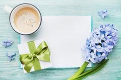 Mutter-Tagesfrühlingsfeiertagskarte mit leerem Notizbuch für Grußtext mit Tasse Kaffee, Geschenk oder Präsentkarton und Hyazinthe lizenzfreie stockfotografie