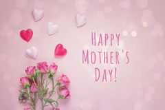 Mutter-Tagesmitteilung mit Blumenstrauß von Rosen und von Herzen auf einem rosa b Stockbilder
