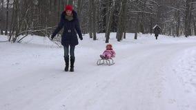Mutter trägt Kind in der kalten Winterzeit Mutterschaft, Spiel 4K stock footage