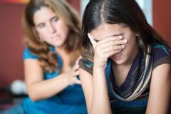 Mutter tröstet ihre jugendlich Tochter Stockfotos