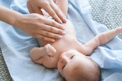 Mutter tut eine Körpermassage ein neugeborenes Baby an lizenzfreie stockfotografie