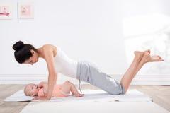 Mutter tut Gymnastik mit ihrem Baby Lizenzfreies Stockfoto