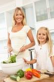Mutter u. Tochter, die Salat in der Küche zubereiten Stockbild