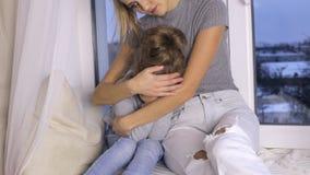 Mutter umarmt ihre nette junge Tochter stock footage