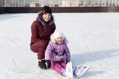 Mutter umarmt ihre schöne Tochter im Winter auf der Eisbahn Stockfotografie