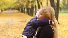 Mutter umarmt leicht ihren Sohn im Herbst Park stock video