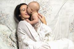 Mutter umarmt zart ihr Kind Stockbild