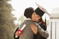 Mutter-und Absolvent-Umarmung lizenzfreie stockbilder