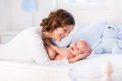 Mutter und Baby auf einem weißen Bett Stockbilder