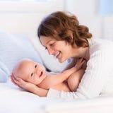 Mutter und Baby auf einem weißen Bett Lizenzfreie Stockfotografie