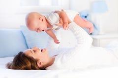Mutter und Baby auf einem weißen Bett Stockfotografie