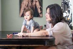 Mutter und Baby bei Tisch Lizenzfreie Stockfotos