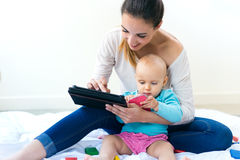 Mutter und Baby, das zu Hause digitale Tablette verwendet Stockbilder