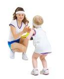 Mutter und Baby in der Tenniskleidung, die Tennis spielt Stockfotografie