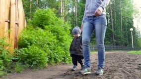 Mutter und Baby, die auf Landlandstraße im Kiefernwald, Fokus auf nettem Kleinkind gehen stock video footage