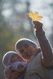 Mutter und Baby, die das gelbe Ahornblatt betrachten Stockbild