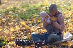 Mutter und Baby, die das gelbe Ahornblatt betrachten Lizenzfreies Stockfoto