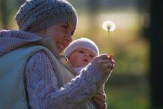 Mutter und Baby, die den Löwenzahn betrachten Stockfoto