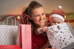 Mutter und Baby, die in der Weihnachtseinkaufstasche schauen lizenzfreies stockfoto