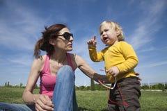 Mutter und Baby, die im Park sprechen Lizenzfreie Stockfotografie