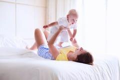 Mutter und Baby, die im weißen Schlafzimmer sich entspannen Stockfotografie