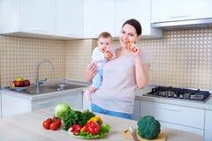 Mutter und Baby, die Karotte in der Küche essen stockbild