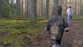 Mutter und Baby, die in Kiefernwald gehen, Spaß haben und durch einen gefallenen Baum klettern stock footage